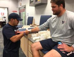 Jeffrey Rodriguez, a Stephen F. Austin State University athletic training graduate student and intern, tapes the wrist of an offensive lineman for the NFL's Houston Texans. Rodriguez, an Austin native, is one of only five U.S. students selected to participate in the summer internship with the Houston Texans.