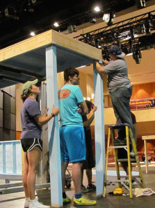 Baytown senior Taylor Dobbs (on ladder), assistant scenic designer, assembles sets with the help of student crews.