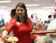 Stephen F. Austin State University Phi Upsilon Omicron member Jessalyn Welch serves salads to guests attending a 1950s-themed Valentine's Day event. Recently, students in SFA's School of Human Sciences Phi U honor society partnered with Carolyn Johnson of Heart to Heart Hospice to host the annual community service project at the First Baptist Church Fellowship Hall.
