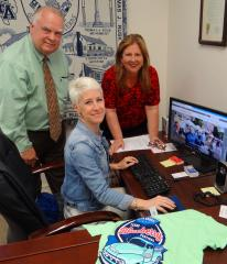 Nacogdoches County Chamber of Commerce CEO Wayne Mitchell views a draft of the Texas Blueberry Festival Weekend micro-site designed by Nacogdoches CVB Marketing Director Sherri Skeeters, sitting, and Director of Sales Joanna Temple. (Photo by Kelly Daniel)