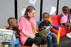 "Stephen F. Austin State University student Kayla King reads ""What a Wonderful World"" to children during the recent ""Passport to DiverCity"" event at the Greater East Texas Community Action Program Head Start campus. SFA students in the School of Human Sciences collaborated with GETCAP Head Start to host an event to celebrate diversity."
