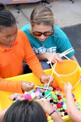 "Stephen F. Austin State University student Azea Gluff helps children from Nacogdoches' Greater East Texas Community Action Program Head Start use chopsticks during a game at the ""Passport to DiverCity"" event. Various stations were set up with cultural games, food and activities."