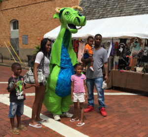 A family poses with the SFA School of Theatre's trademark dragon character Schlaftnicht at the Texas Blueberry Festival in downtown Nacogdoches. A variety of costumed fairy tale characters will be at this year's festival on June 10.