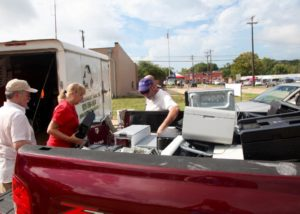 Keep Nacogdoches Beautiful directors (left to right) Mike Keller, Cheryl Bartlett and Mark Holl unload several recycled technology items from a participant's truck.