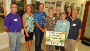 The Pattersons pose for a photo with the Landscape Leadership Award along with their extended family and friends, Keep Nacogdoches Beautiful members, and Garden Capital of Texas Committee members. (From left to right) Mark Holl, Cindy Patterson, Greg Patterson, Brenda Mansfield, Harry Mansfield, Bonnie Orr, Katie Blevins, and Don Orr.