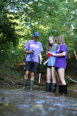 (pictured, from left) Nacogdoches High School seniors Brandon Smith, Marin Beal and Miranda Allbee check the turbidity, take the temperature and measure the depth of the water at Lanana Creek for their Stephen F. Austin State University STEM Academy research project. During their fourth year in the academy, students practice experimental design by conducting their own research.