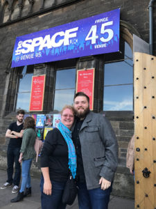 "SFA School of Theatre Professor Angela Bacarisse and former student Bobby Britton '17 pose outside the Edinburgh, Scotland, theatre where Britton's play ""Closed For Repairs"" was presented during the Festival Fringe last August."