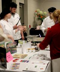 """Samantha Dibilio, Wylie hospitality administration sophomore at Stephen F. Austin State University, explains her group's dishes to """"Book Bites"""" attendees. Students prepared guacamole and homemade tortilla chips, spicy vegetarian chili, and colorful sopapillas to complement the Hispanic book theme."""