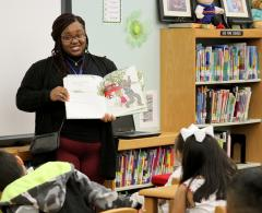 """Stephen F. Austin State University senior Melanie Lynch reads """"Anna Hibiscus' Song"""" by Atinuke and Lauren Tobia to a group of Brooks-Quinn-Jones Elementary School students during the National African-American Read-In. SFA students and faculty members also read poems to students at Nacogdoches High School."""